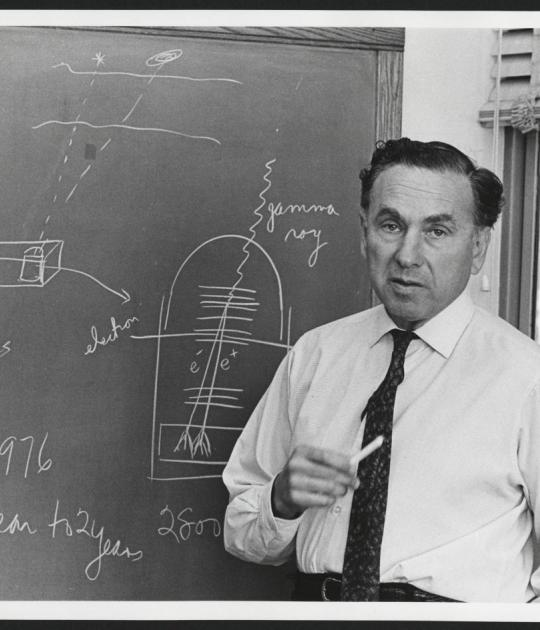 Photo of Robert Hofstadter with in front of chalkboard with physics calculations