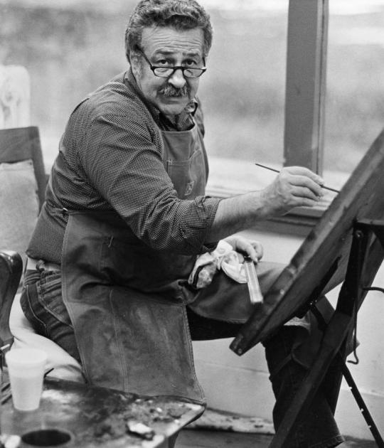 Photo of Nathan Oliveira seated at easel