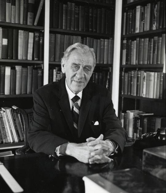Photo of former Stanford University President J.E. Wallace Sterling seated at desk