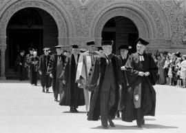 Stanford faculty in regalia walking through arches