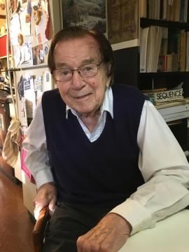 Photo of Charles Drekmeier seated at his kitchen table in 2017