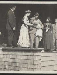 Photo of Almon E. Roth holding a baby on porch of a house with other people gathered around.