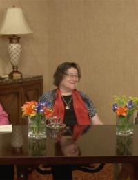 Photo of the four panelists and the moderator seated at a table